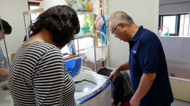 洗濯機の修理をするスタッフ